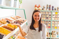 Pretty woman shows dry fruits in grocery shopping stock image