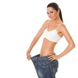 Pretty woman shows her weight loss. By wearing an old jeans, isolated on white background Royalty Free Stock Photo