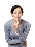 Pretty woman shows silence gesture. Touching her lips, isolated on white Stock Photo