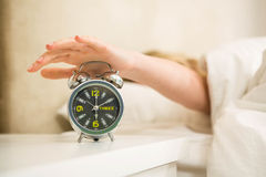 Pretty woman shutting off her alarm clock. In the bedroom stock image