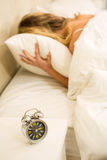 Pretty woman shutting off her alarm clock Royalty Free Stock Photos