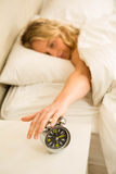 Pretty woman shutting off her alarm clock. In the bedroom stock photo
