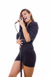 Pretty woman singer holding a microphone singing royalty free stock image