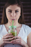 Pretty woman sipping on green juice Royalty Free Stock Photo