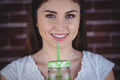 Pretty woman sipping on green juice Stock Photos