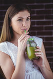 Pretty woman sipping on green juice Royalty Free Stock Image