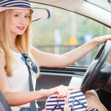 Pretty woman sit in car holds flip flops in hand Stock Images