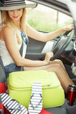 Pretty woman sit in car with suitcase. Summer road trip, travel concept. Pretty woman sit in car with suitcase, ready for the journey on holidays Royalty Free Stock Image