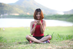 Pretty woman sit on lawn play her smartphone and smile,wide angl Royalty Free Stock Image