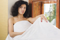 Pretty woman sit near window covered by blanket Stock Photography