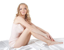 Pretty woman sit on silk bed isolated Royalty Free Stock Images