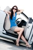 Pretty woman sits in the white car with side door opened Royalty Free Stock Images