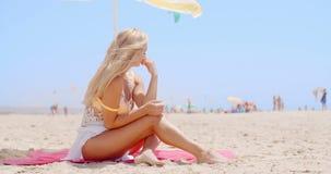 Pretty Woman Sitting at the Beach Under Umbrella stock video