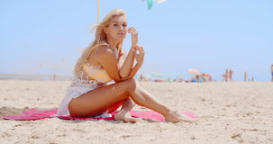 Pretty Woman Sitting at the Beach Under Umbrella stock footage