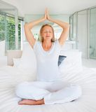 Pretty woman sitting on bed and meditating Stock Photography