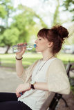 Pretty Woman Sitting at the Bench Drinking Water Stock Image