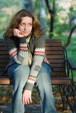 Pretty woman sitting on a bench in park Stock Photos