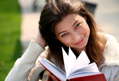 Pretty woman sitting on bench in park reading book Royalty Free Stock Photos