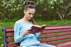 Pretty woman reading a book in the park. Pretty woman sitting on a bench in the park and reading a book Stock Images