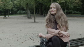 Pretty  woman sitting on a bench in a park waiting for someone. Closeup. stock footage