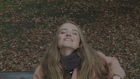 Pretty  woman sitting on a bench in a park waiting for someone. Closeup. stock video footage