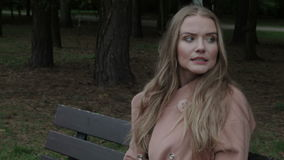 Pretty  woman sitting on a bench in a park waiting for someone. Closeup. stock video