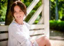 Pretty Woman Sitting on Bench Smiling at You Royalty Free Stock Images