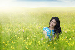 Pretty woman sitting on blossom meadow Royalty Free Stock Photo