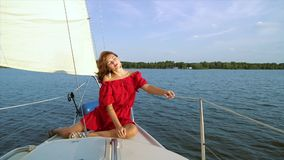 Pretty woman sitting on bow of sailing boat. Pretty young woman in red dress sitting on bow of sailing boat during river voyage. Girl in luxury outfit enjoying stock video