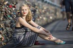 Pretty  woman sitting on bridge of love in Krakow. Stock Photo