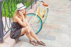 Pretty woman sitting at bridge near vintage bicycle, typing sms Royalty Free Stock Photography