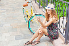 Pretty woman sitting at bridge near vintage bicycle, typing sms Stock Images