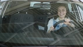 Pretty woman sitting in car and listening to salesman in automobile center. slow-motions Royalty Free Stock Photos