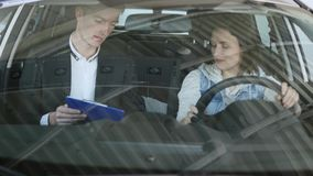 Pretty woman sitting in car and listening to salesman in automobile center. slow-motions Stock Photography