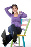 Pretty woman sitting on a colorful chair Royalty Free Stock Images