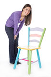 Pretty woman sitting on a colorful chair Stock Photo