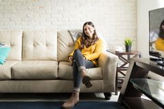 Pretty Woman Sitting Comfortably On Sofa. Good looking woman smiling while relaxing on couch at home stock photos