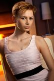 Pretty woman sitting in cosy room. With mysterious look stock photography