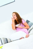 Pretty woman sitting on couch and eating muesli Royalty Free Stock Photography