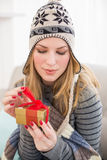 Pretty woman sitting on a couch while opening a gift box Royalty Free Stock Images