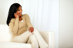 Pretty woman sitting on couch talking on cellphone Stock Photo
