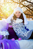 Pretty woman sitting on the couch in winter park Stock Photos