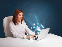 Pretty woman sitting at desk and typing on laptop with diagrams Royalty Free Stock Images