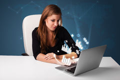 Pretty woman sitting at desk and typing on laptop with diagrams Royalty Free Stock Image