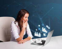 Pretty woman sitting at desk and typing on laptop with diagrams Stock Photography