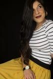Pretty woman sitting down yellow skirt black background Stock Image