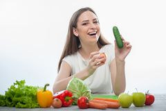 Pretty woman is sitting with fruits and vegetables Stock Images