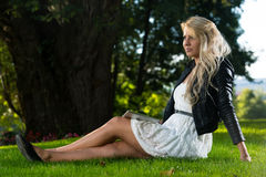 Pretty Woman Sitting On The Grass With Digital Tablet Stock Photography