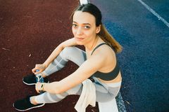 Pretty woman sitting on the ground with a bottle of water after Jogging outdoors royalty free stock photo