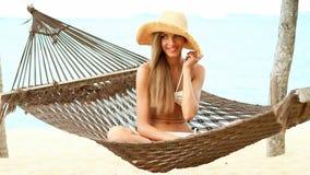 Pretty woman sitting on hammock at the beach. Pretty woman sitting on hammock at the tropical beach stock footage